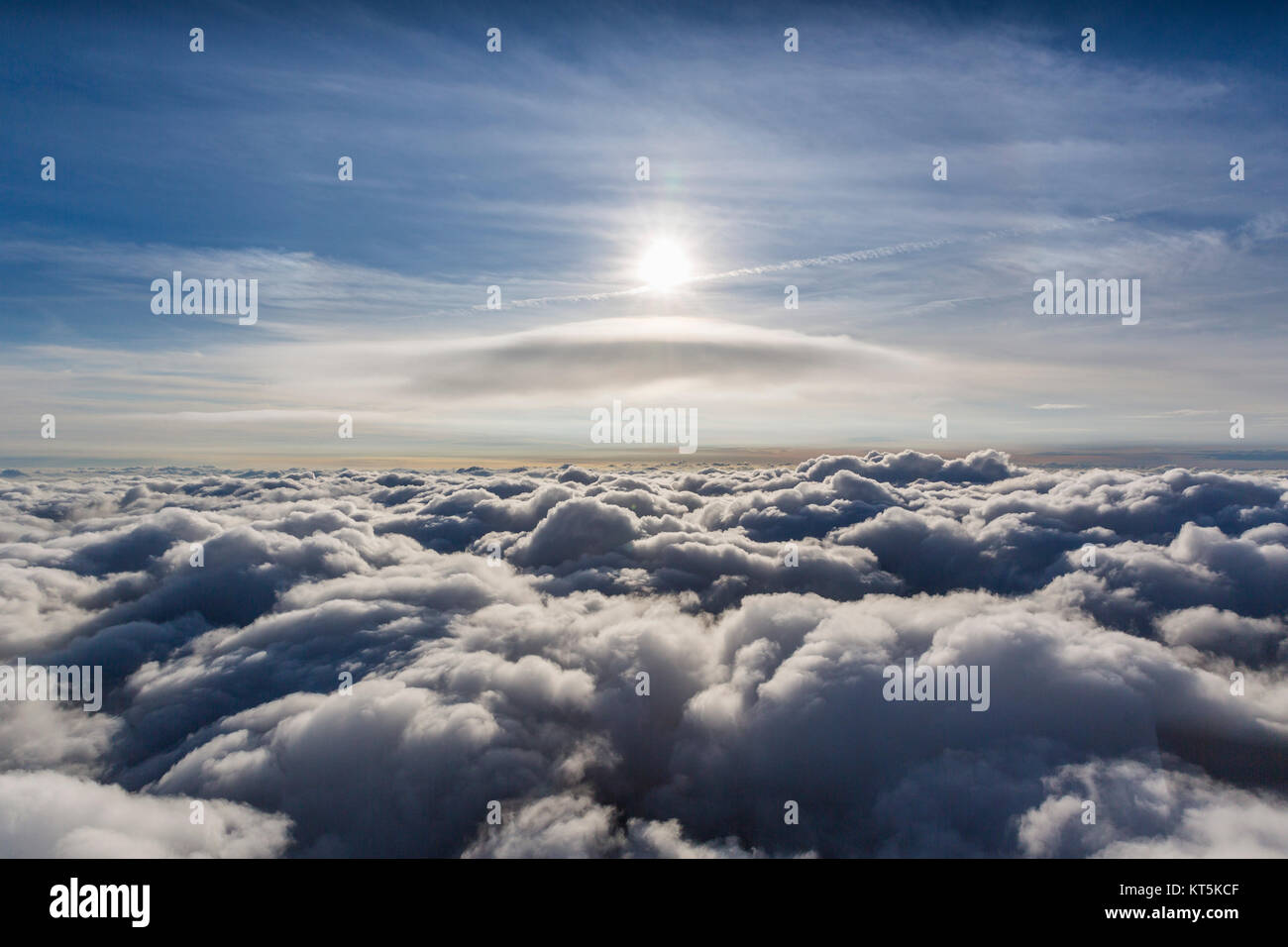 Lenticular cloud above the uppermost cloud layer, cumulus lenticularis, clouds and sun, cloud flight over the northern Stock Photo