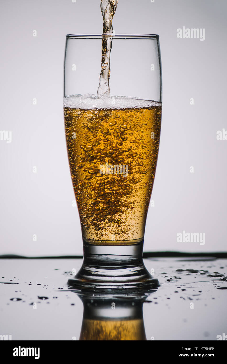 pouring light beer into transparent glass Stock Photo