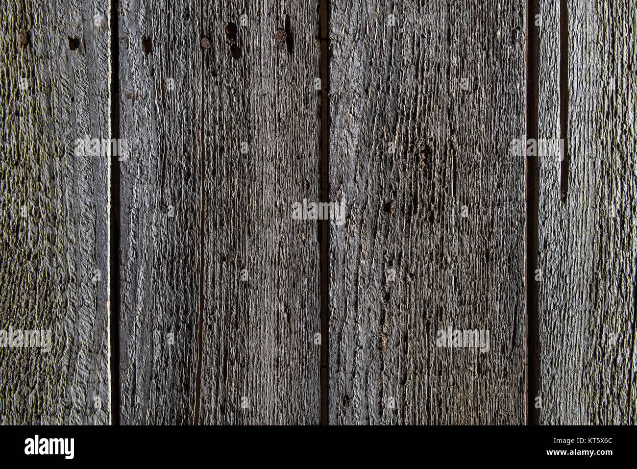 full frame of dark wooden background with vertical planks - Stock Image