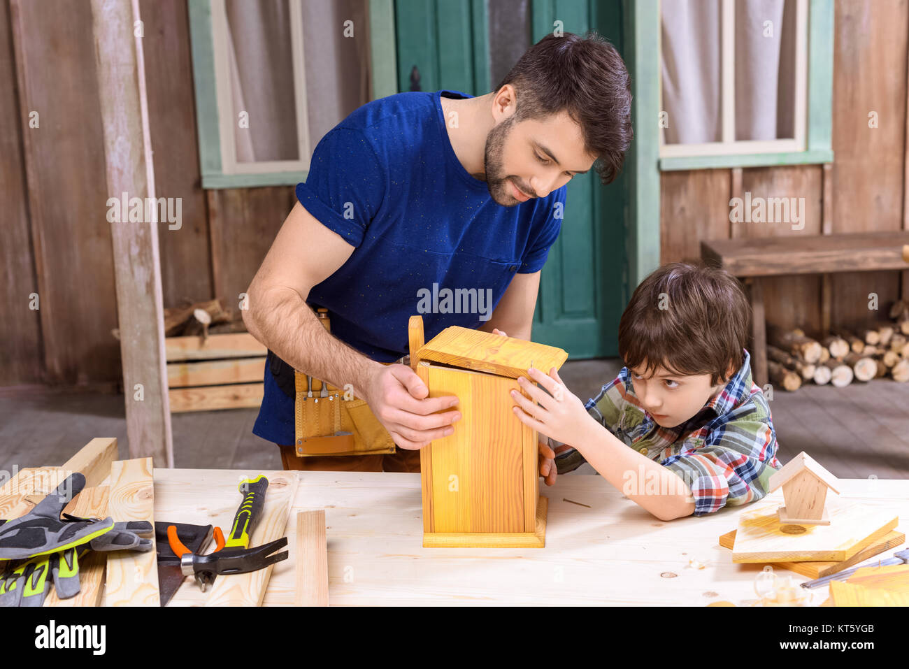 Concentrated father and son making wooden birdhouse together - Stock Image