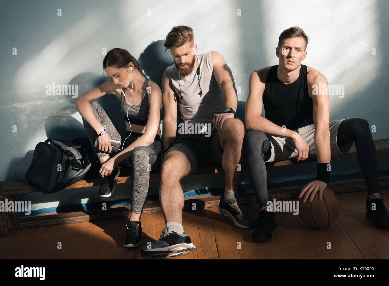 tired smiling sporty men and woman sitting on bench in gym - Stock Image