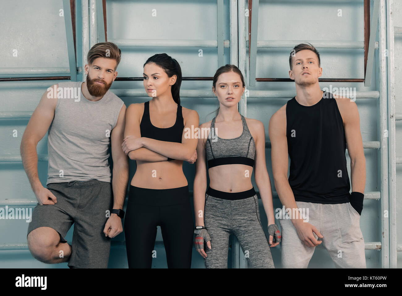 confident sporty men and women in gym - Stock Image