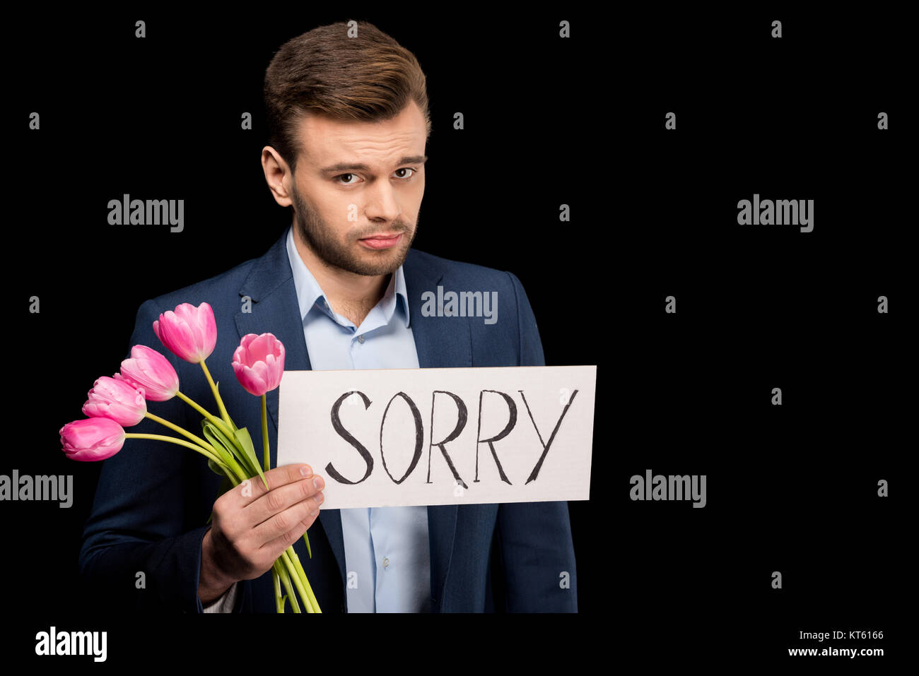 Ashamed young man with tulips and sorry sign looking at camera - Stock Image