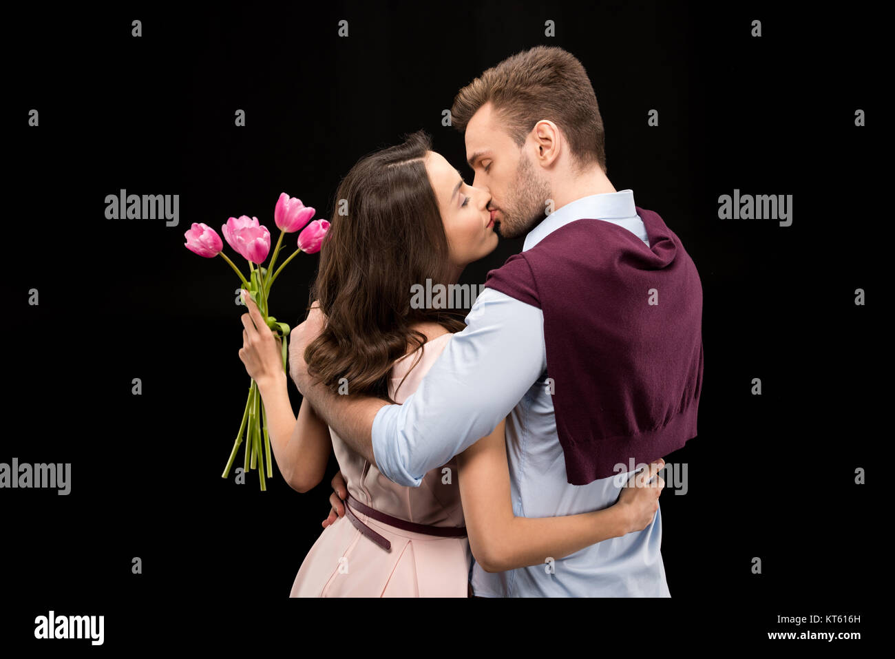 back view of man kissing woman with tulips bouquet on black, international womens day concept - Stock Image