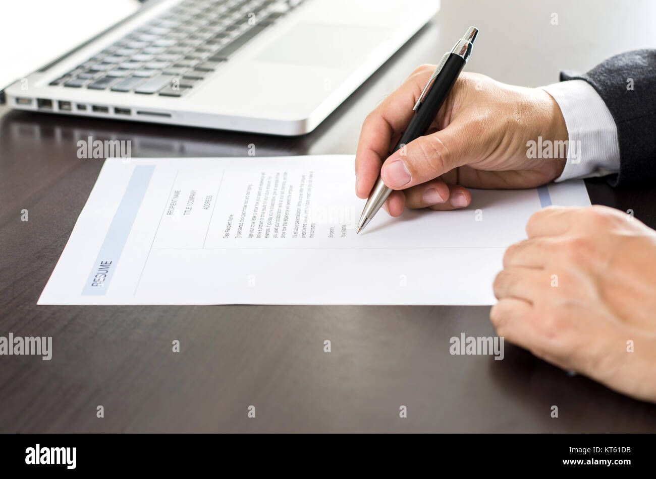 Close-up man signing of on resume form. - Stock Image