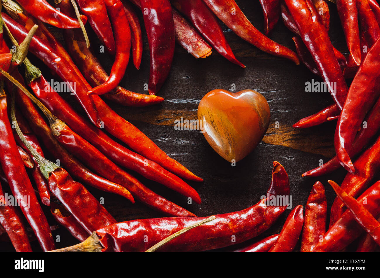 Dried Cayenne Peppers with Petrified Wood Heart - Stock Image