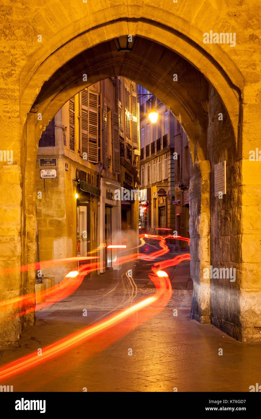 Car light-trails through entry gate to Place de l'Hotel de Ville at night, Aix-en-Provence, France - Stock Image