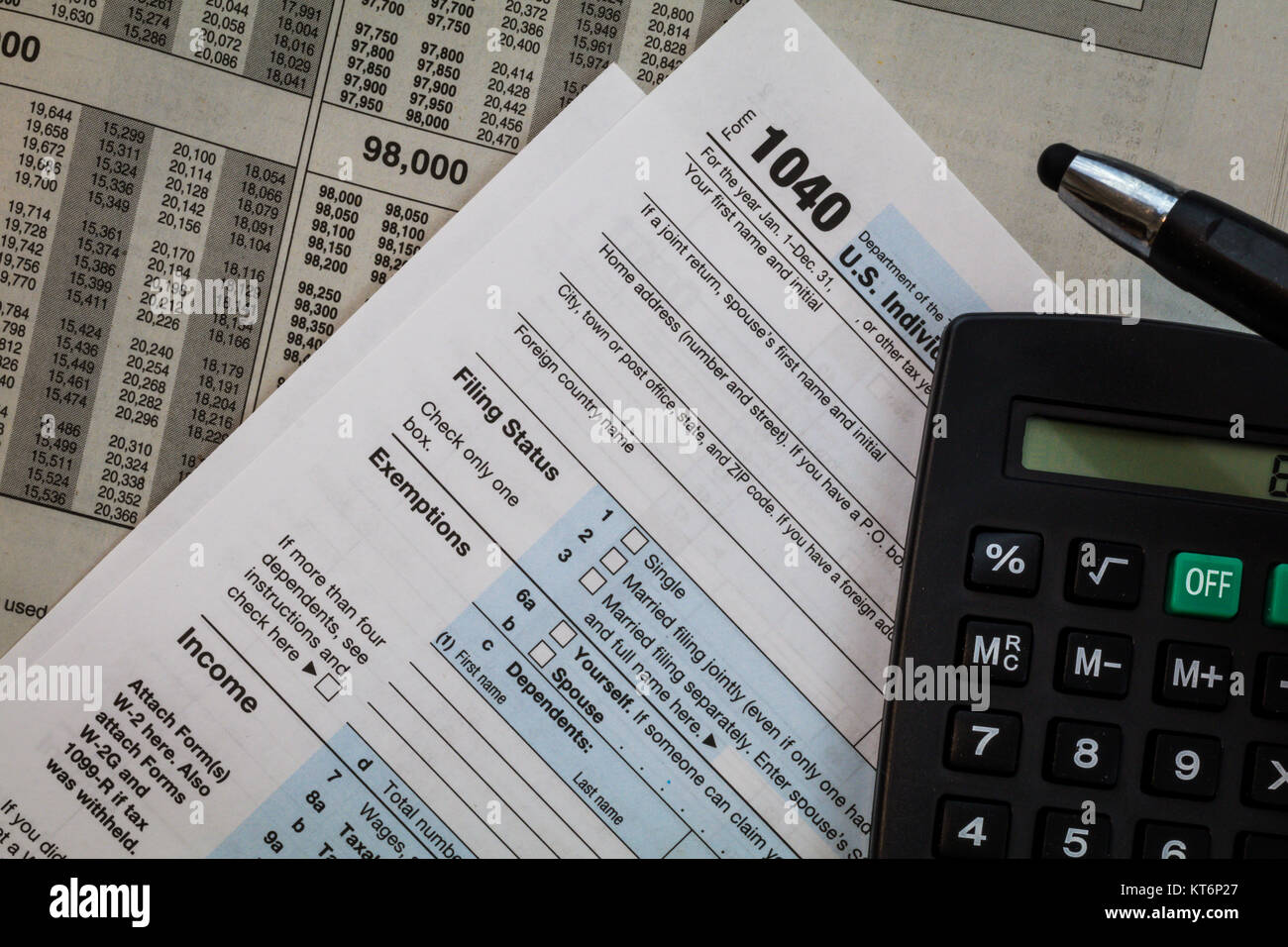 Save Download Preview Tax preparation form US 1040 and tax tables with pen and calculator, generic (no year specified) - Stock Image