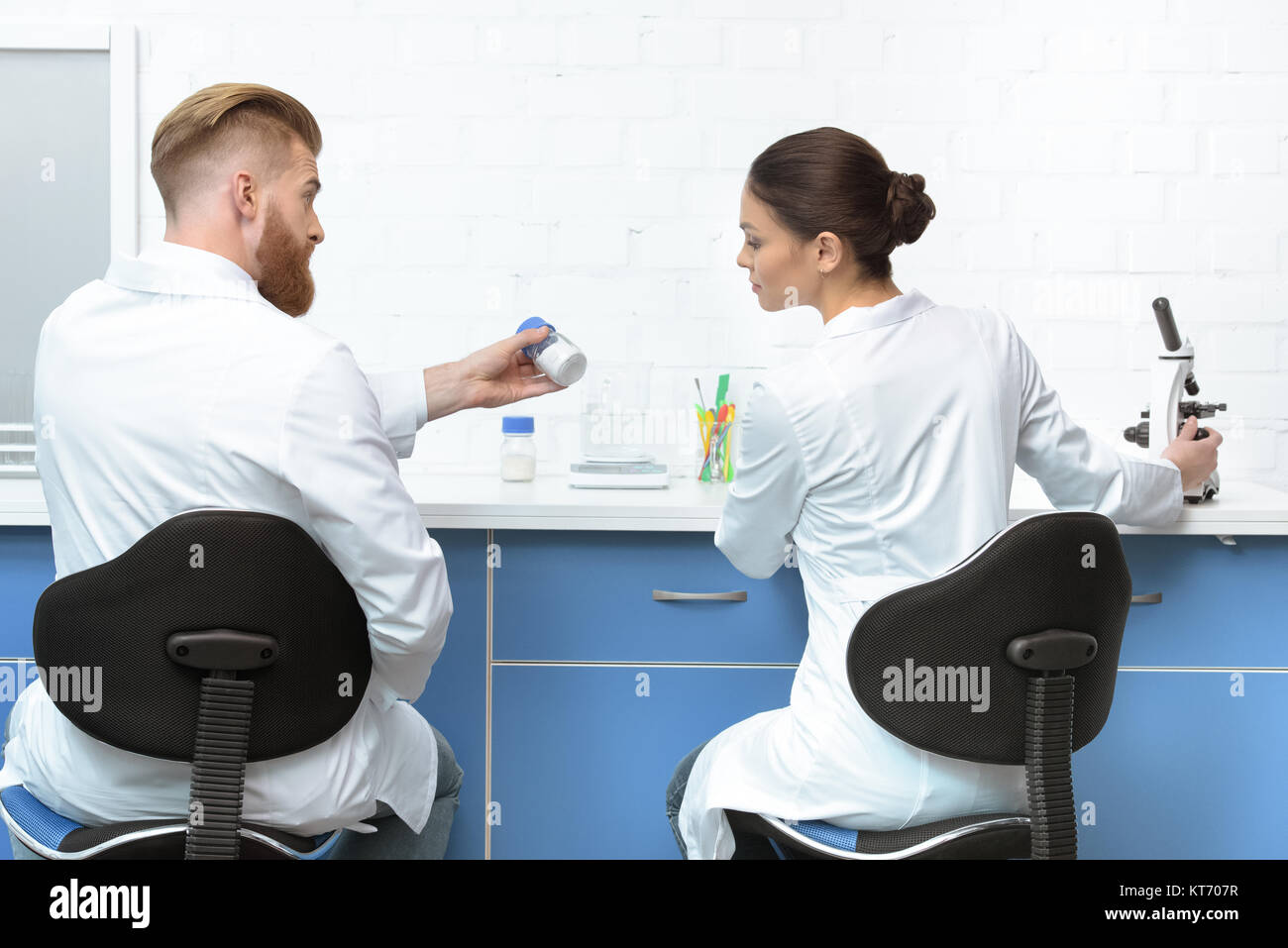 back view of scientists discussing analysis during work in lab - Stock Image