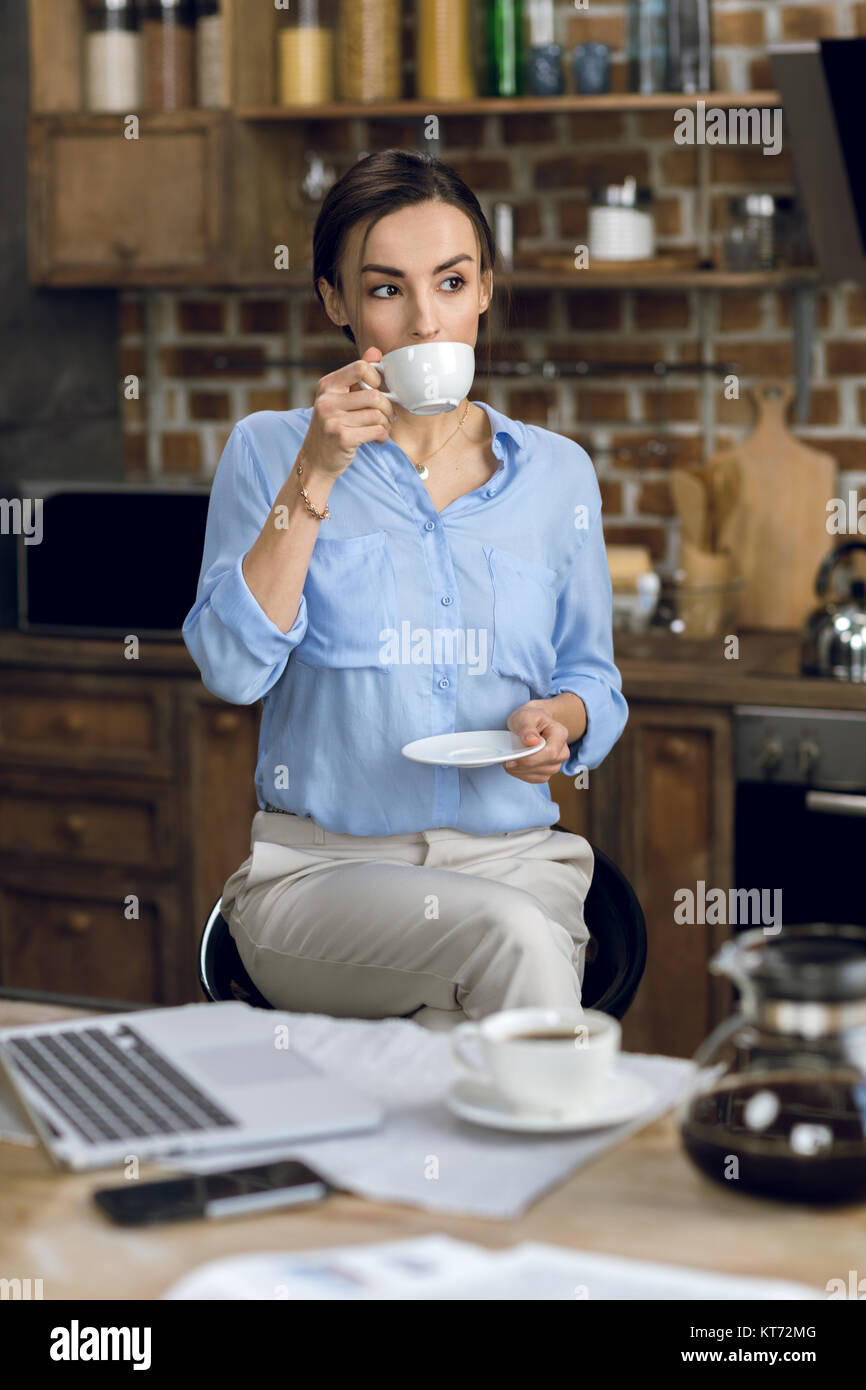 Attractive young businesswoman drinking coffee at morning Stock Photo