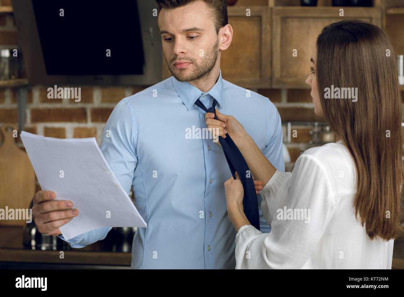businessman reading documents while wife tying tie - Stock Image