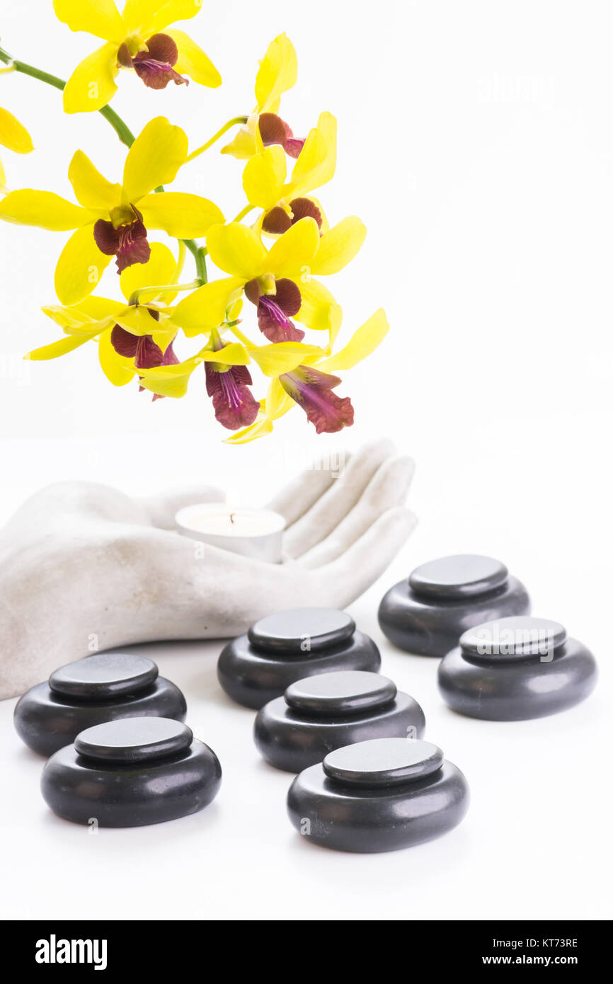 Spa concept with hot stones and tea light close up - Stock Image