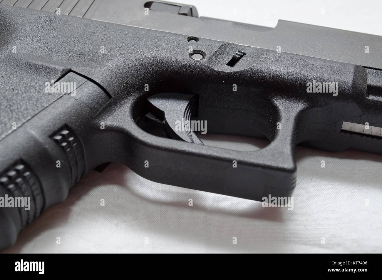 A close up of a black semi automatic pistol, showing the trigger, trigger guard, grip and ejection port - Stock Image