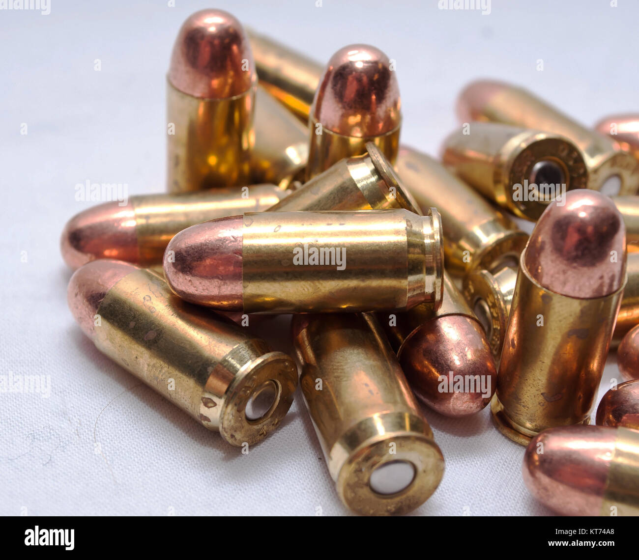 A pile of .45 caliber bullets on a white background - Stock Image