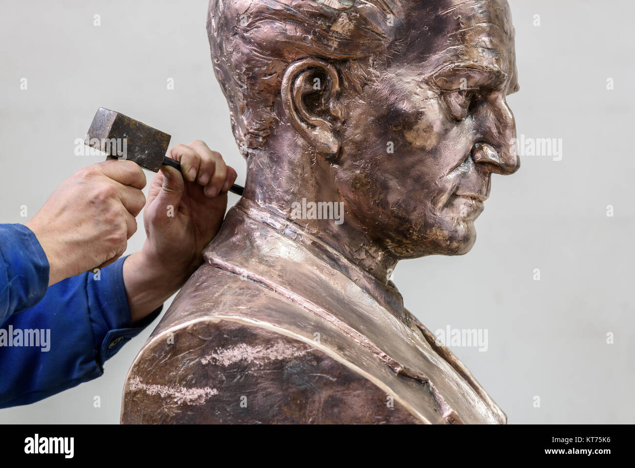 Sculptor working. Adding the finishing touches to the bust of a male figure. - Stock Image