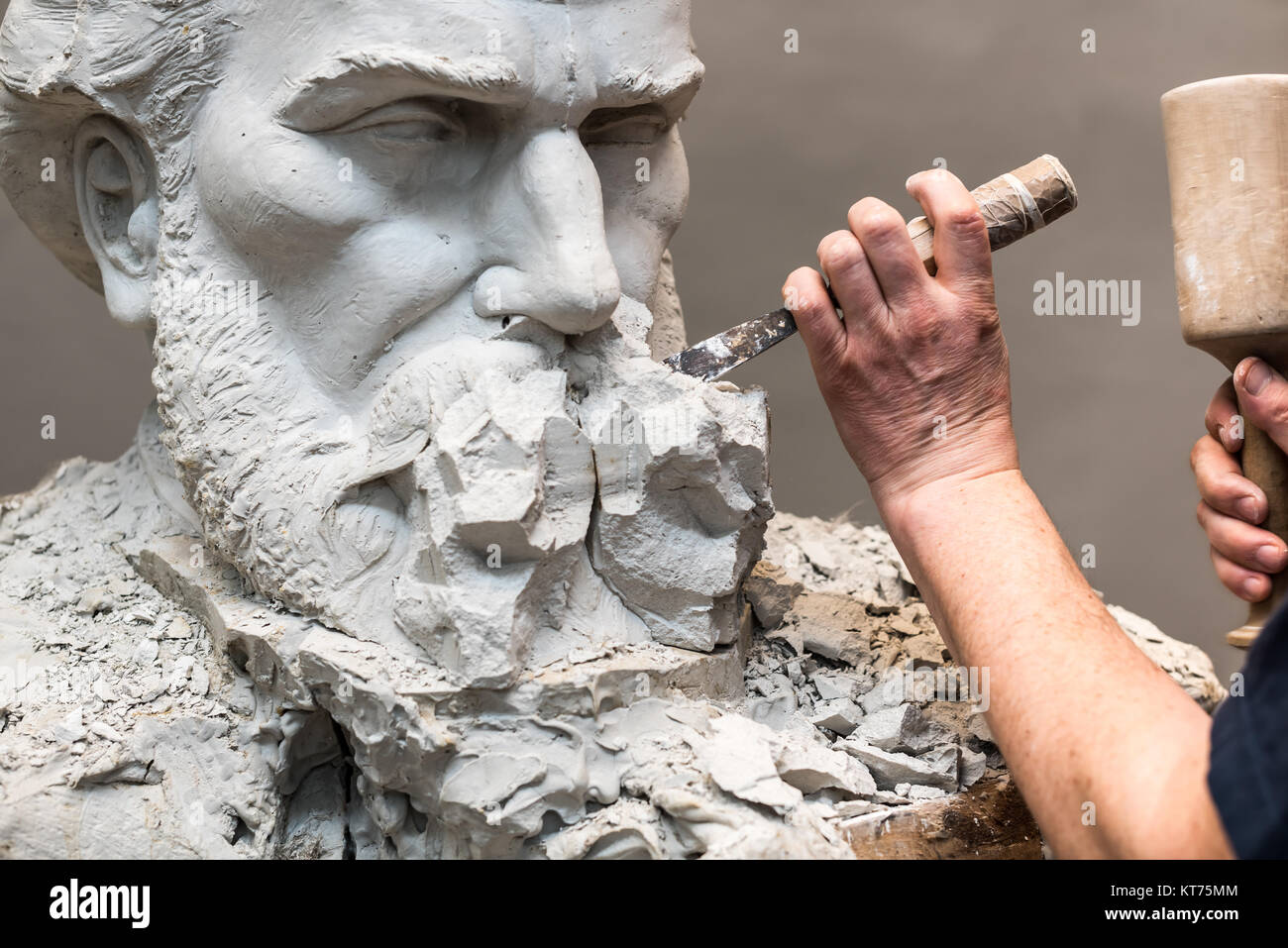 Positive Negative Form. Hands of sculptor and hammer detail while carving. - Stock Image