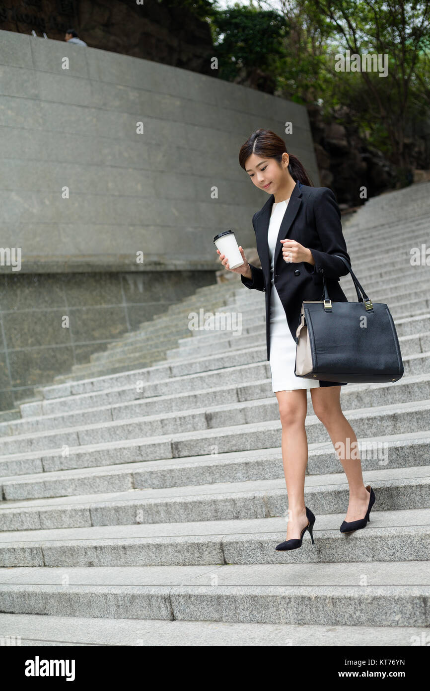 Asian Business woman going down the stair - Stock Image
