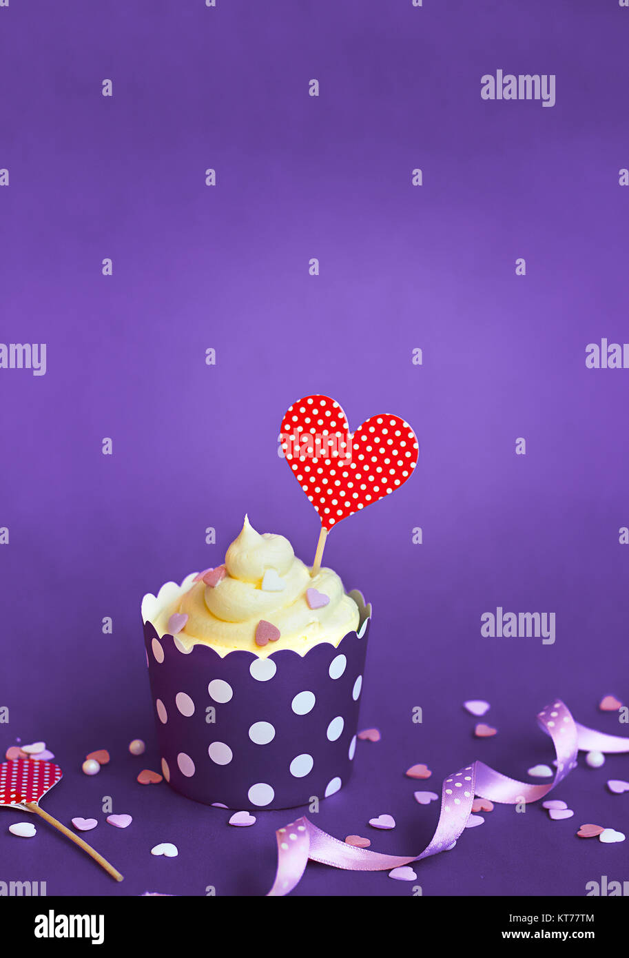 Vanilla cupcake with small decorative hearts and red heart topper, in violet baking paper cup, against violet background - Stock Image