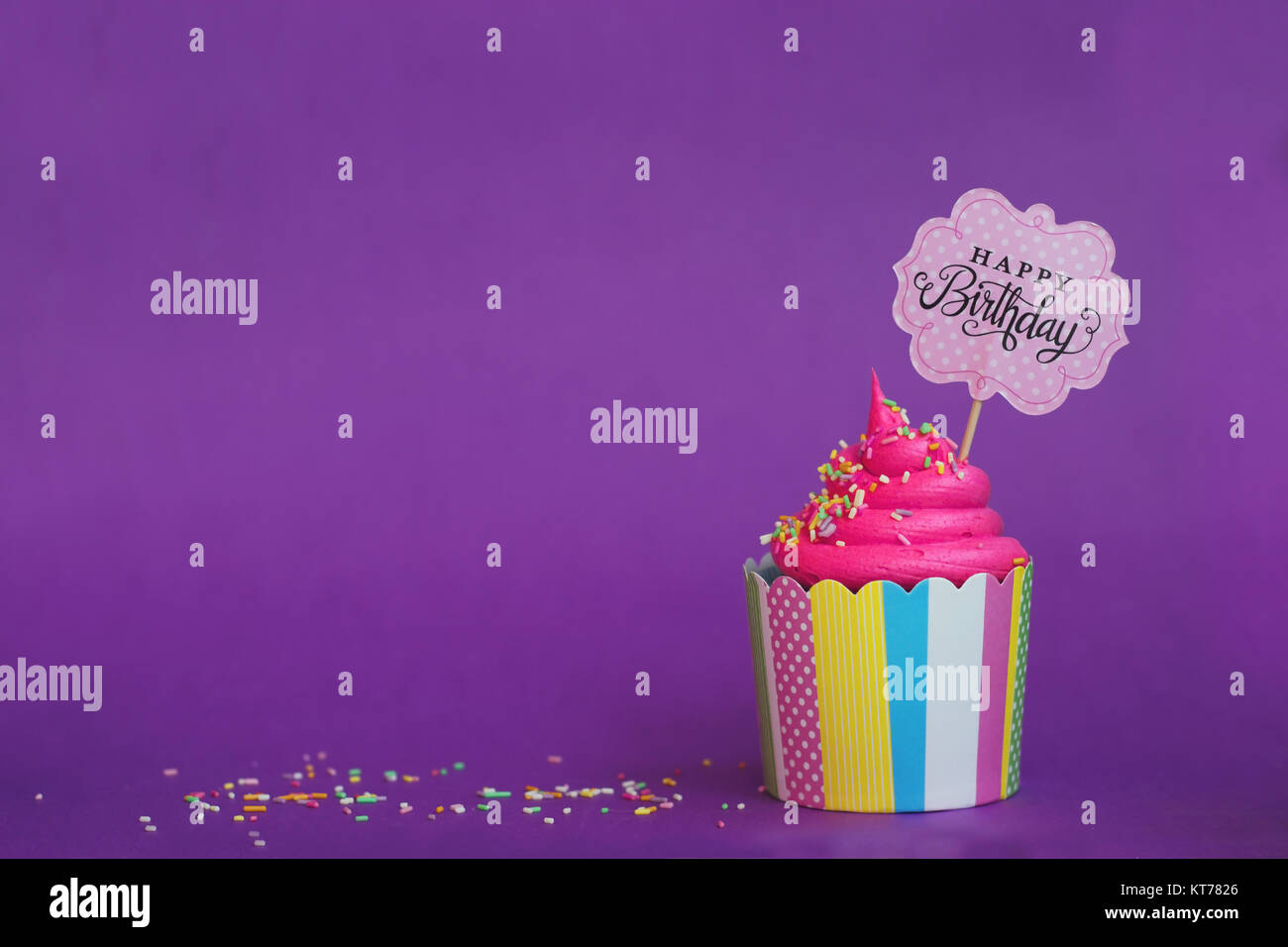 tasty strawberry cupcake with sprinkles and happy birthday banner on