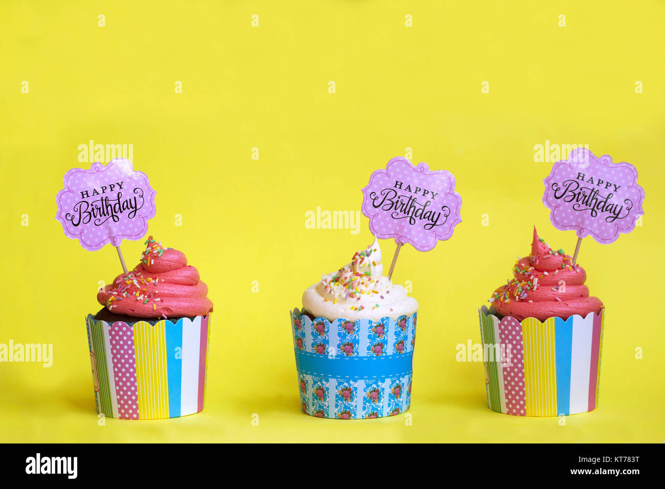 Three tasty strawberry cupcakes in colorful paper baking cups, with Happy Birthday greeting card, on yellow background. - Stock Image