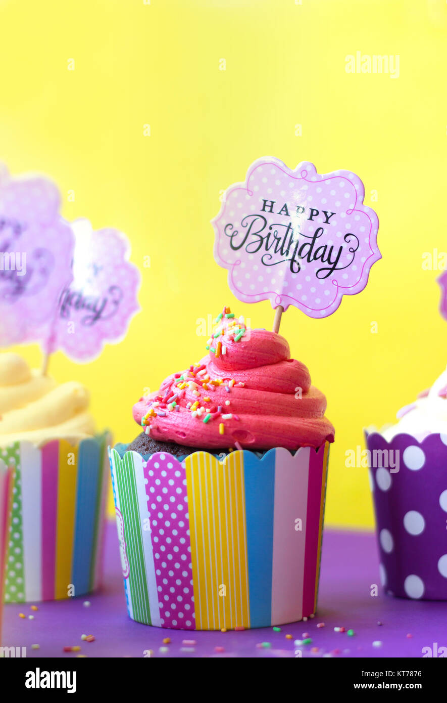 Tasty strawberry cupcakes in colorful paper baking cups, with Happy Birthday greeting card, on yellow background. - Stock Image