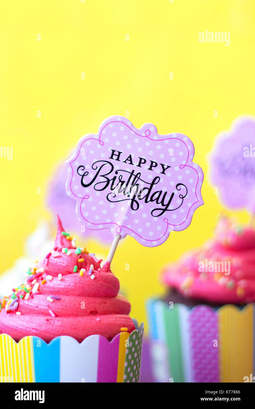 Tasty strawberry cupcakes with Happy Birthday greeting card on yellow background. Party background - Stock Image