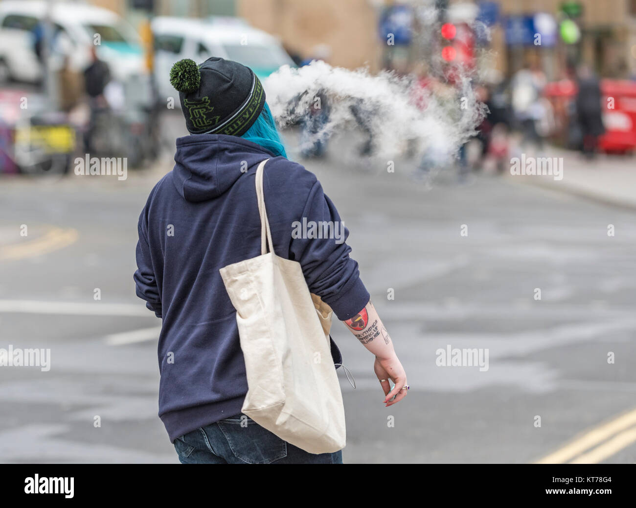 Woman walking away smoking an electronic cigarette, causing excessive smoke and polluting the atmosphere, in the - Stock Image