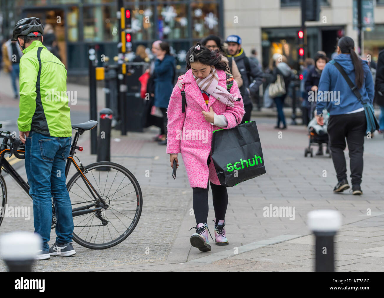 Young Asian woman dressed in expensive looking clothing in Winter, in the busy city of Brighton, East Sussex, England, - Stock Image