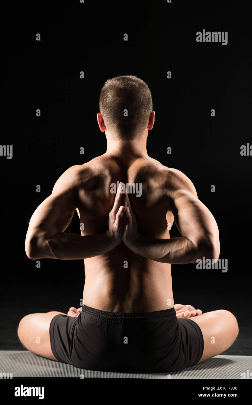 Man sitting in yoga position - Stock Image