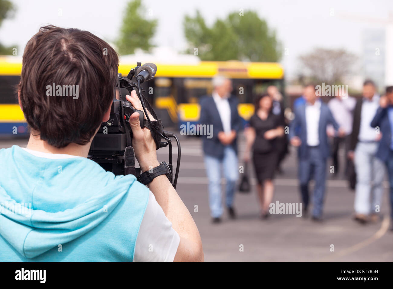 Cameraman filming unrecognizable group of people - Stock Image