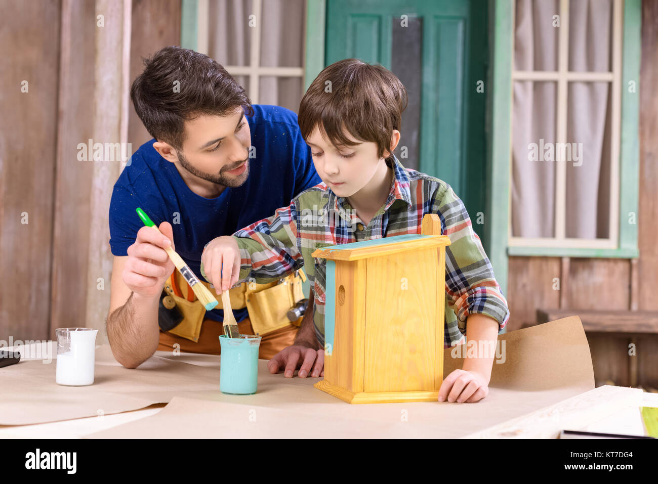 Concentrated father and son painting wooden birdhouse together - Stock Image