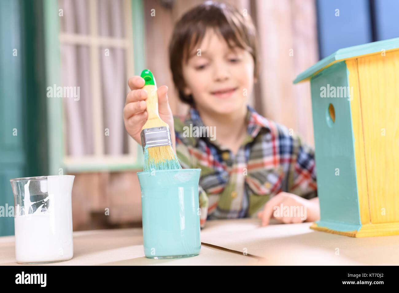 Cute smiling boy holding paintbrush while painting handmade birdhouse - Stock Image