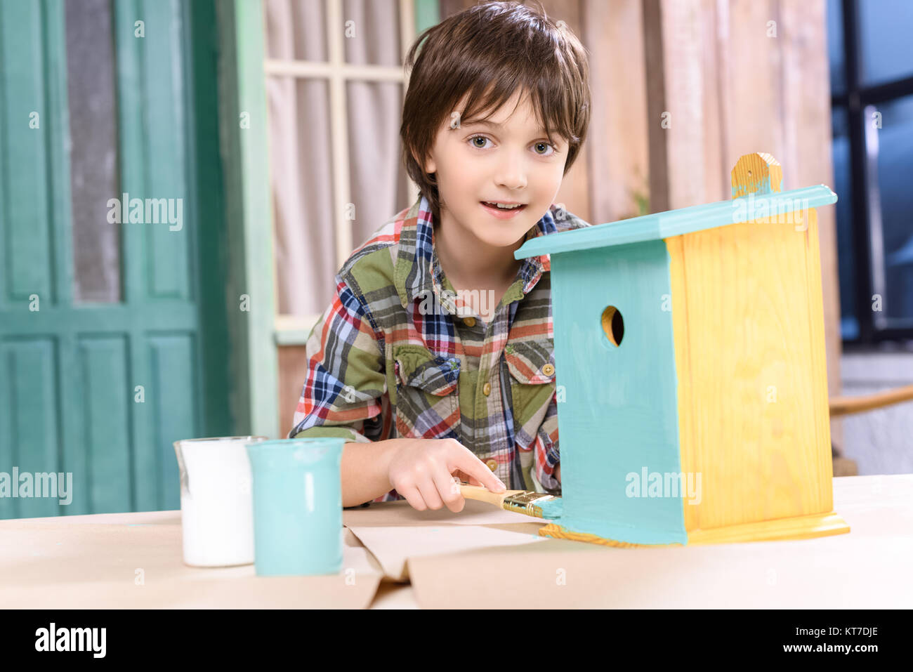 Cute little boy painting wooden birdhouse and smiling at camera - Stock Image