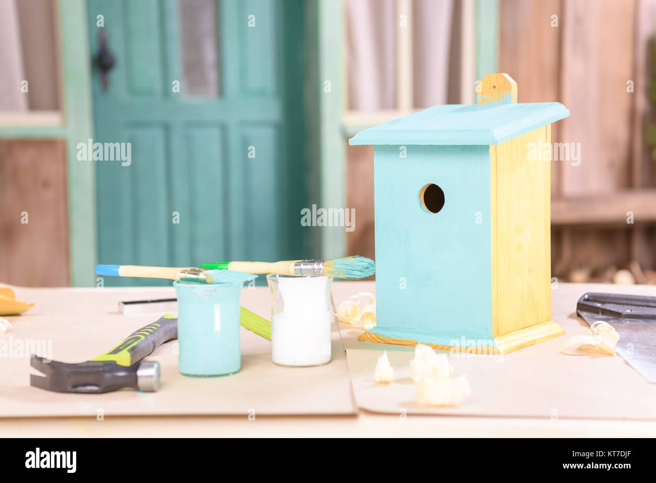 Close-up view of handmade small birdhouse with paints and tools on table - Stock Image
