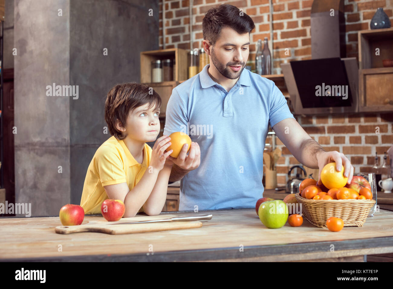 Father and son selecting fruits from basket at kitchen table Stock Photo