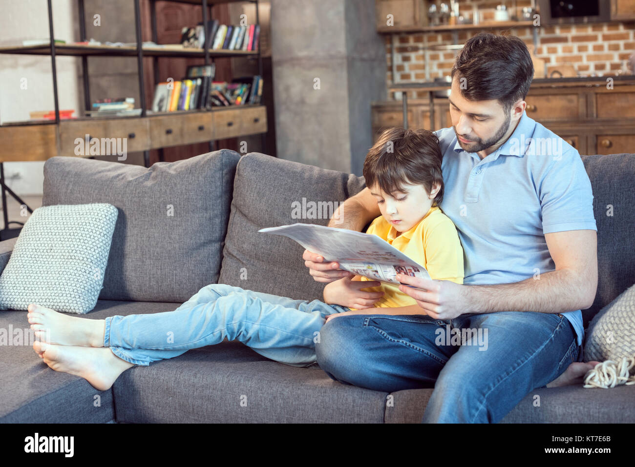 focused father and son reading newspaper together at home - Stock Image