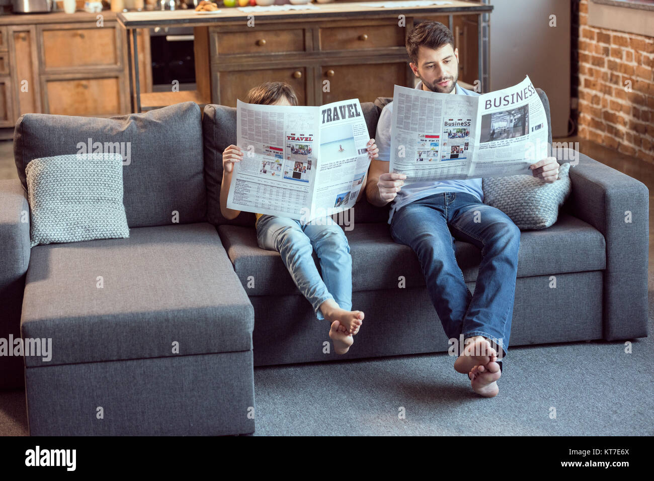 father and son sitting on couch and reading newspapers - Stock Image