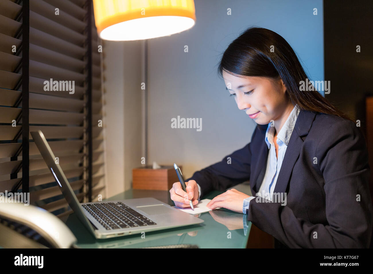 Businesswoman writing on paper with laptop computer - Stock Image