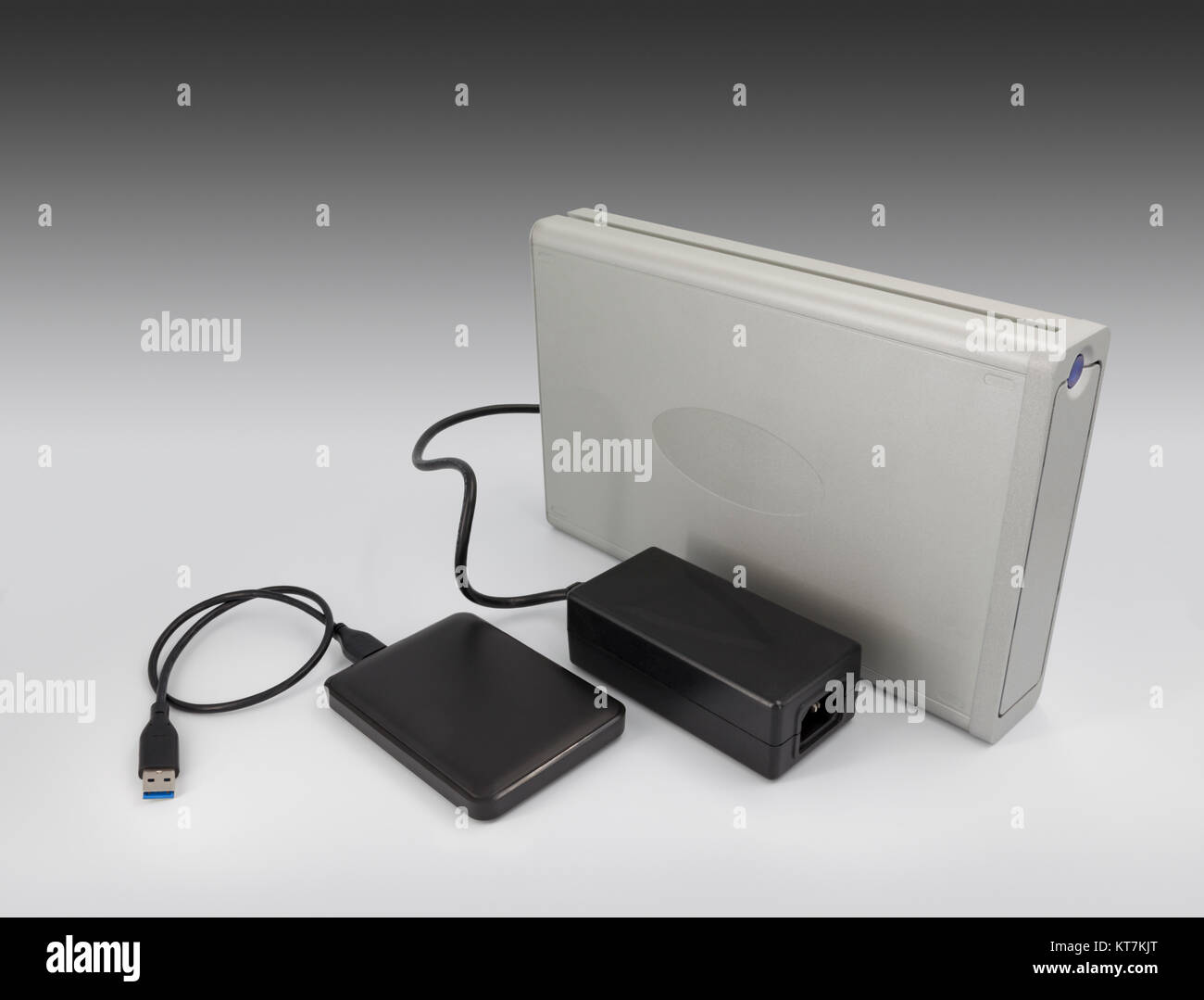 A comparison between hard-drive computer technology within 10 years showing one large hard metal case and one small - Stock Image