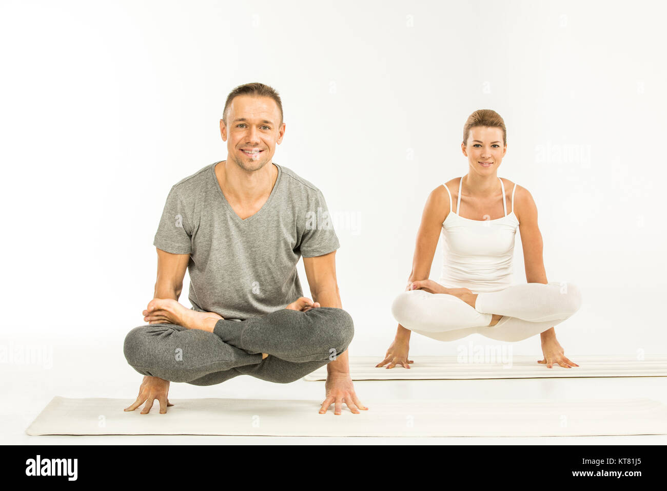 Couple sitting in yoga position - Stock Image