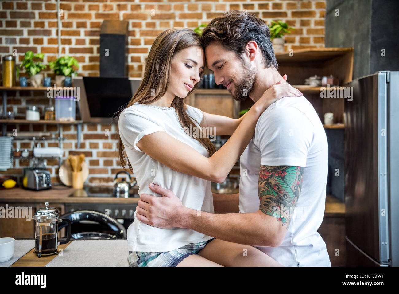 Couple hugging in kitchen - Stock Image
