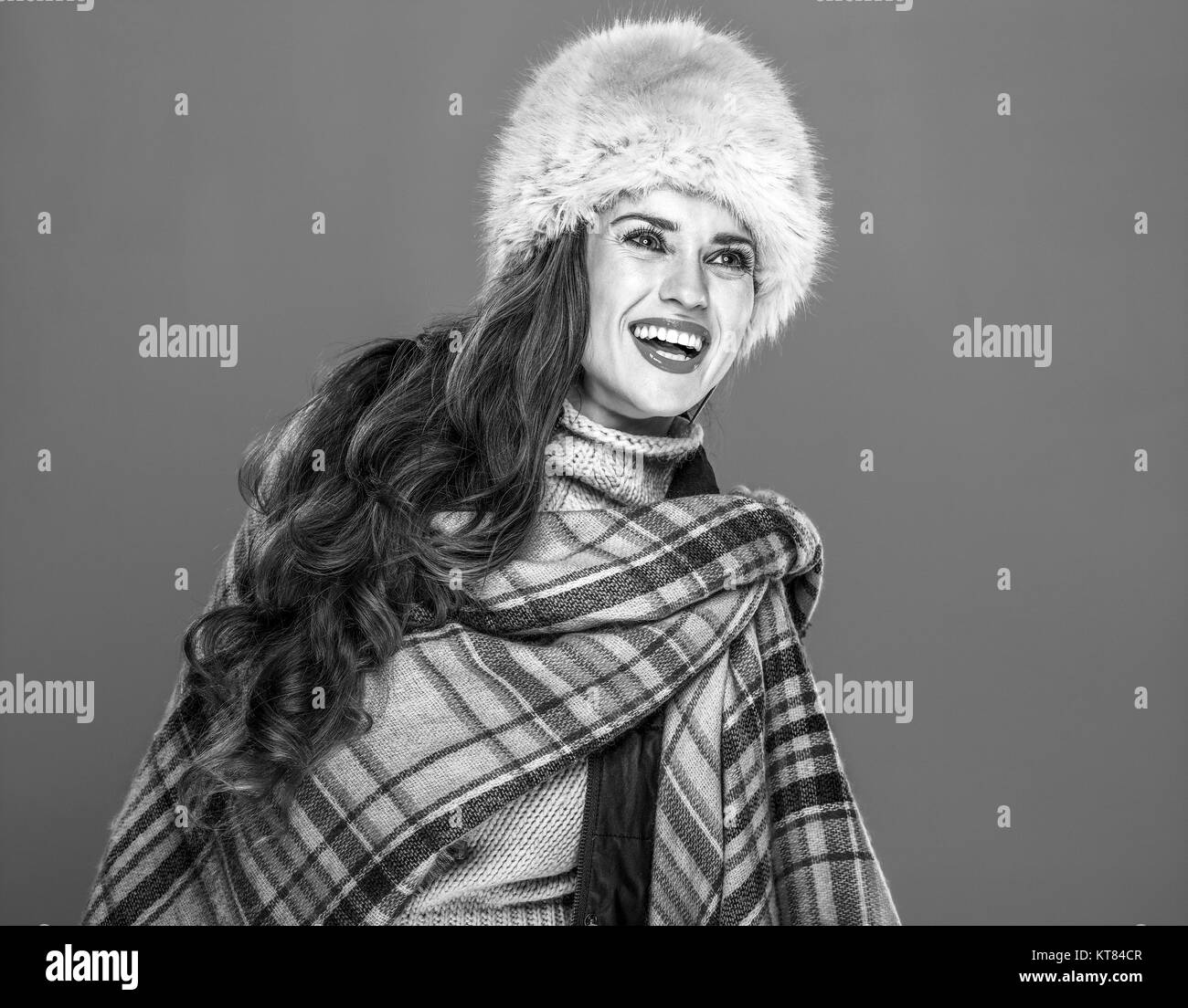 Winter things. Portrait of happy young woman in fur hat isolated on cold blue background looking on copy space - Stock Image