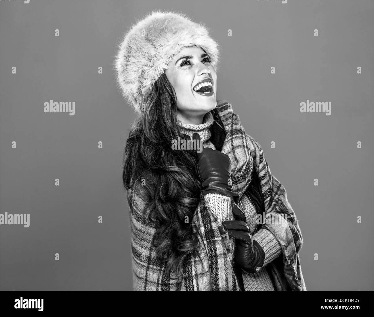 Winter things. Portrait of happy modern woman in fur hat isolated on cold blue background looking on copy space - Stock Image