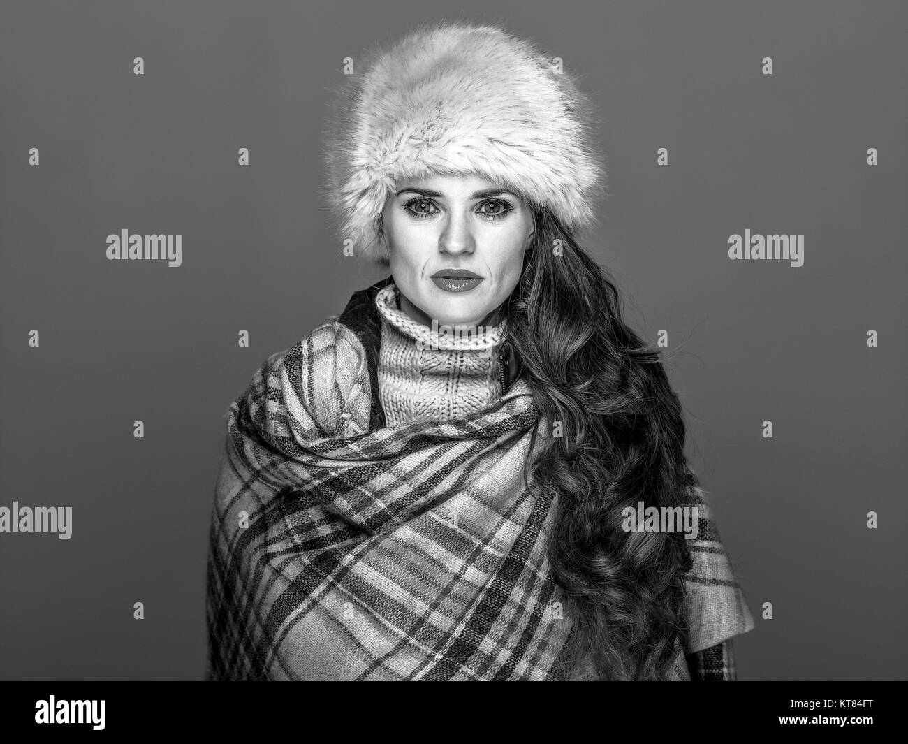 Winter things. Portrait of young elegant woman in fur hat isolated on cold blue background - Stock Image