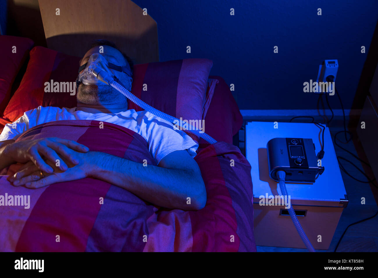 A man with sleep apnea syndrome, wears a CPAP mask while sleeping, breathing mask that presses air into the airways - Stock Image