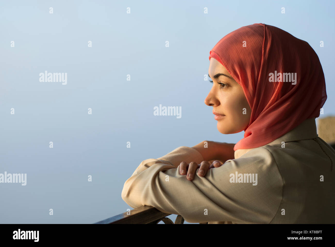 Muslim woman wearing hijab looking away outdoors - Stock Image