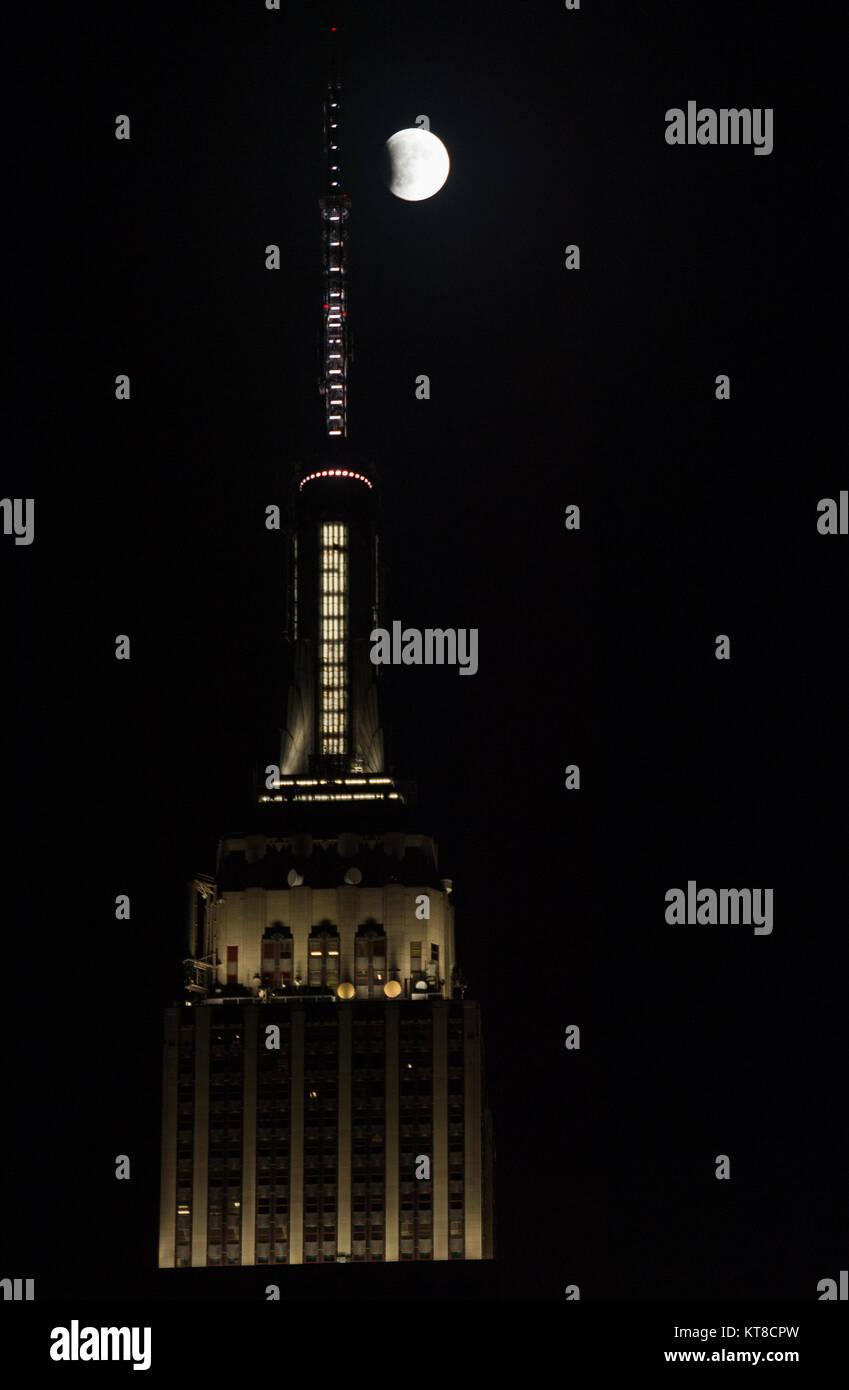 A perigee full moon, or supermoon, is seen next to the Empire State Building at the beginning of a total lunar eclipse, - Stock Image