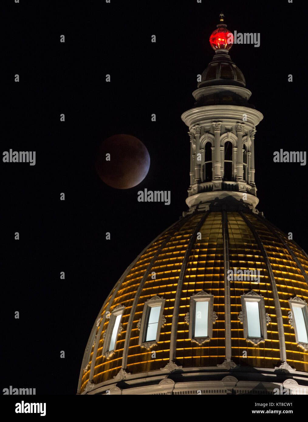 A perigee full moon, or supermoon, is seen during a total lunar eclipse behind the Colorado State Capitol Building - Stock Image