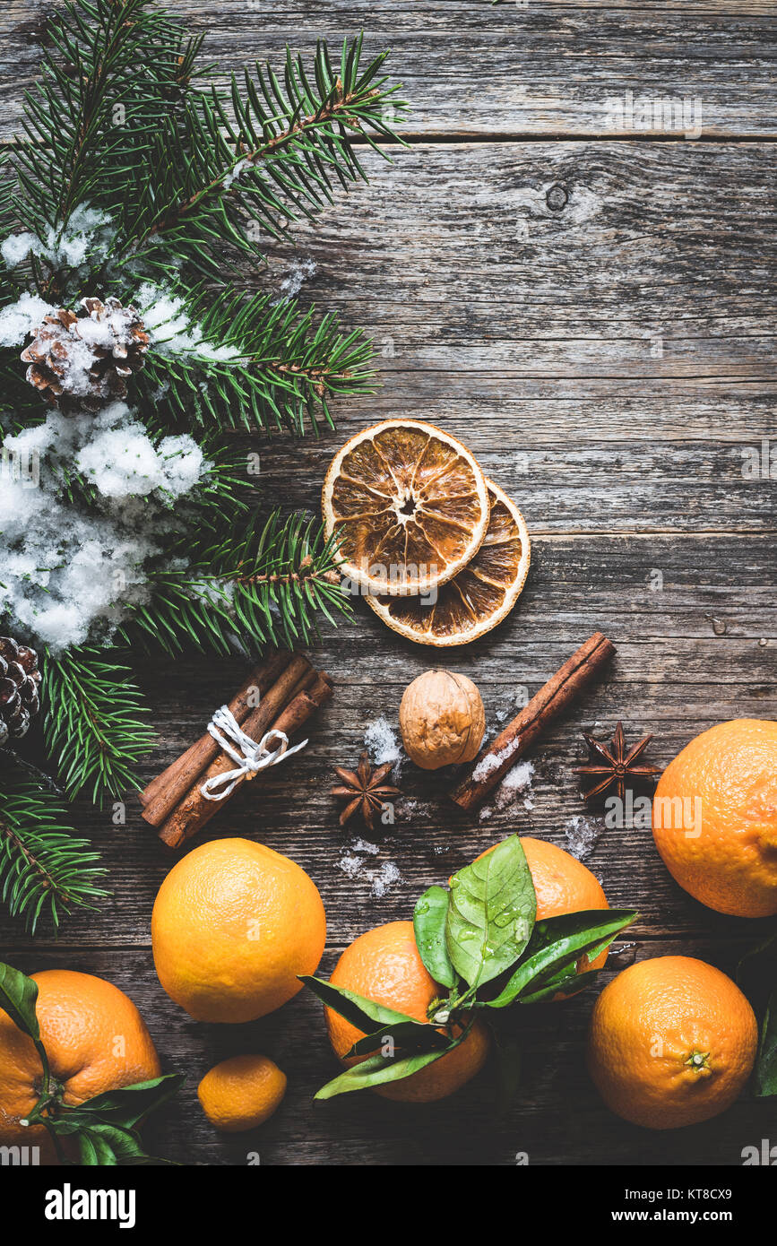 Clementines, fir tree, spices and snow on old wooden background. Christmas winter composition - Stock Image
