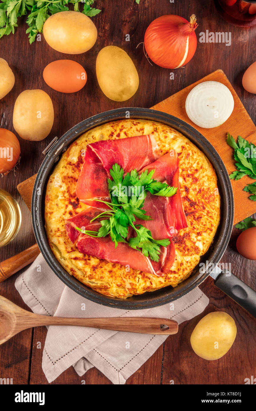 Spanish tortilla with wine, ingredients, and copy space - Stock Image